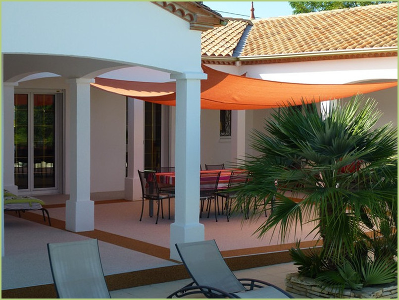 A pretty house with a terrace covered by an orange veil, very nice